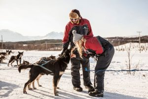 boyfriend and girlfriend on winter holiday cuddle brown husky dog in harness