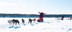 celebrating girl in red parka driving dog sled
