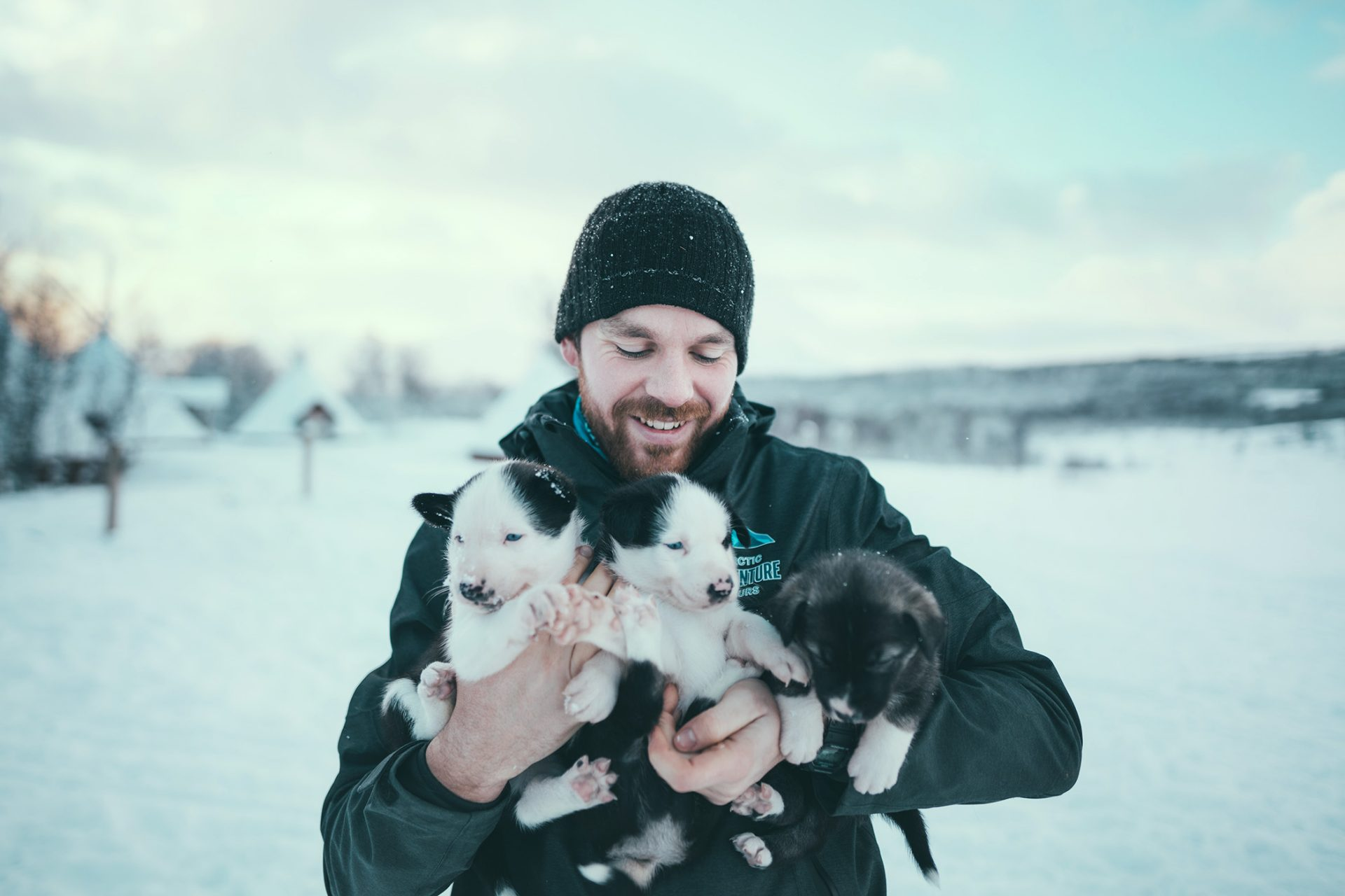man in black hat with two husky puppies