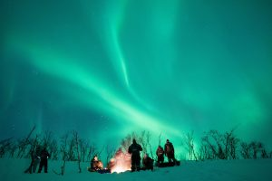 Group around the Campfire with northern lights