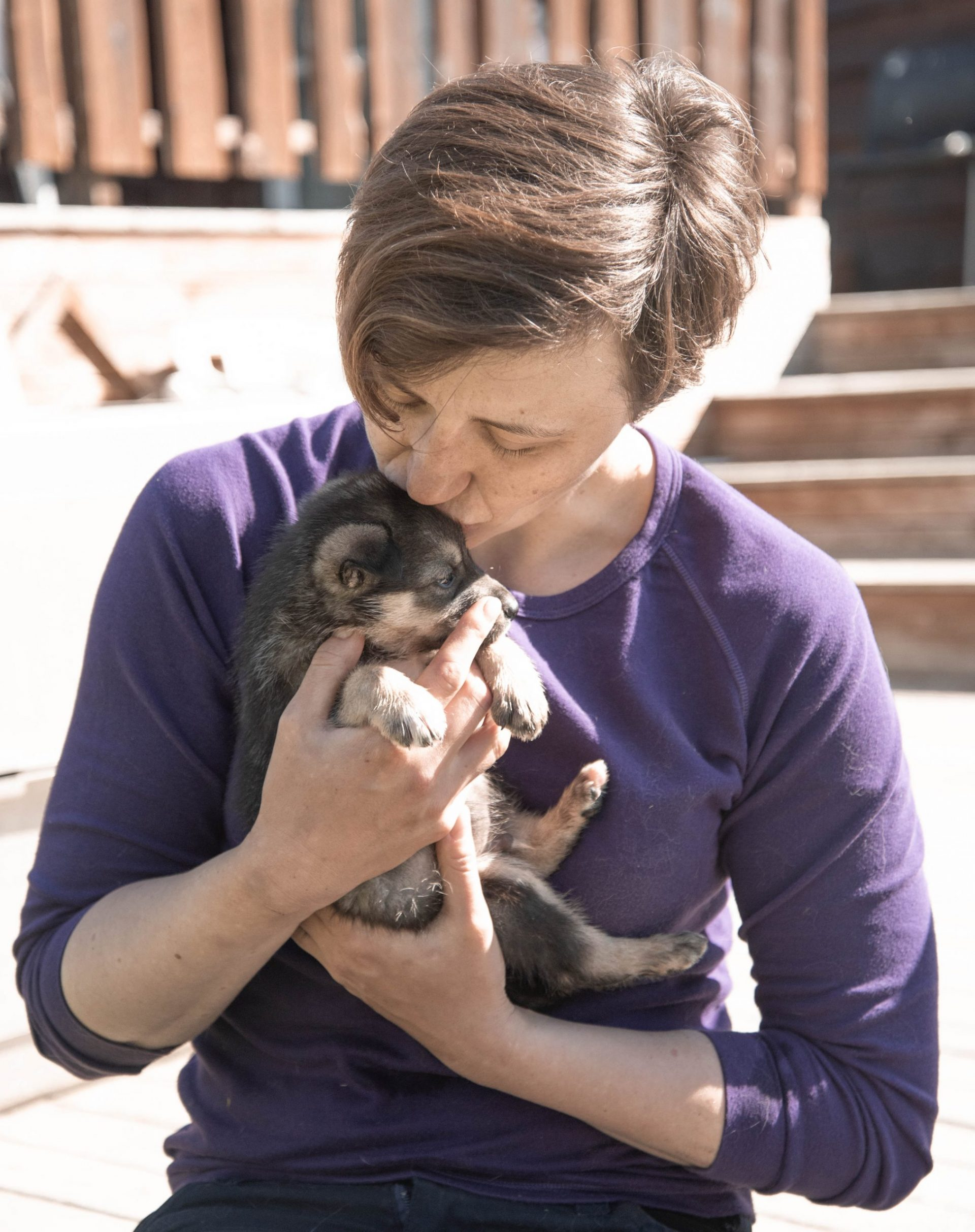 woman kissing small brown puppy