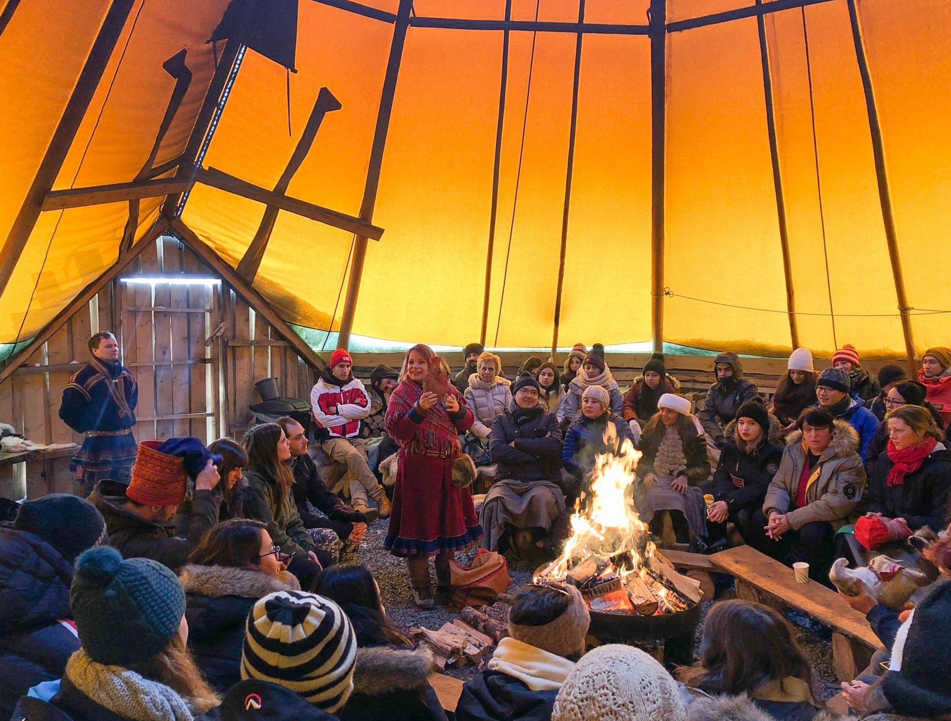 woman giving a lecture in sami lavvo tent with fire Norway