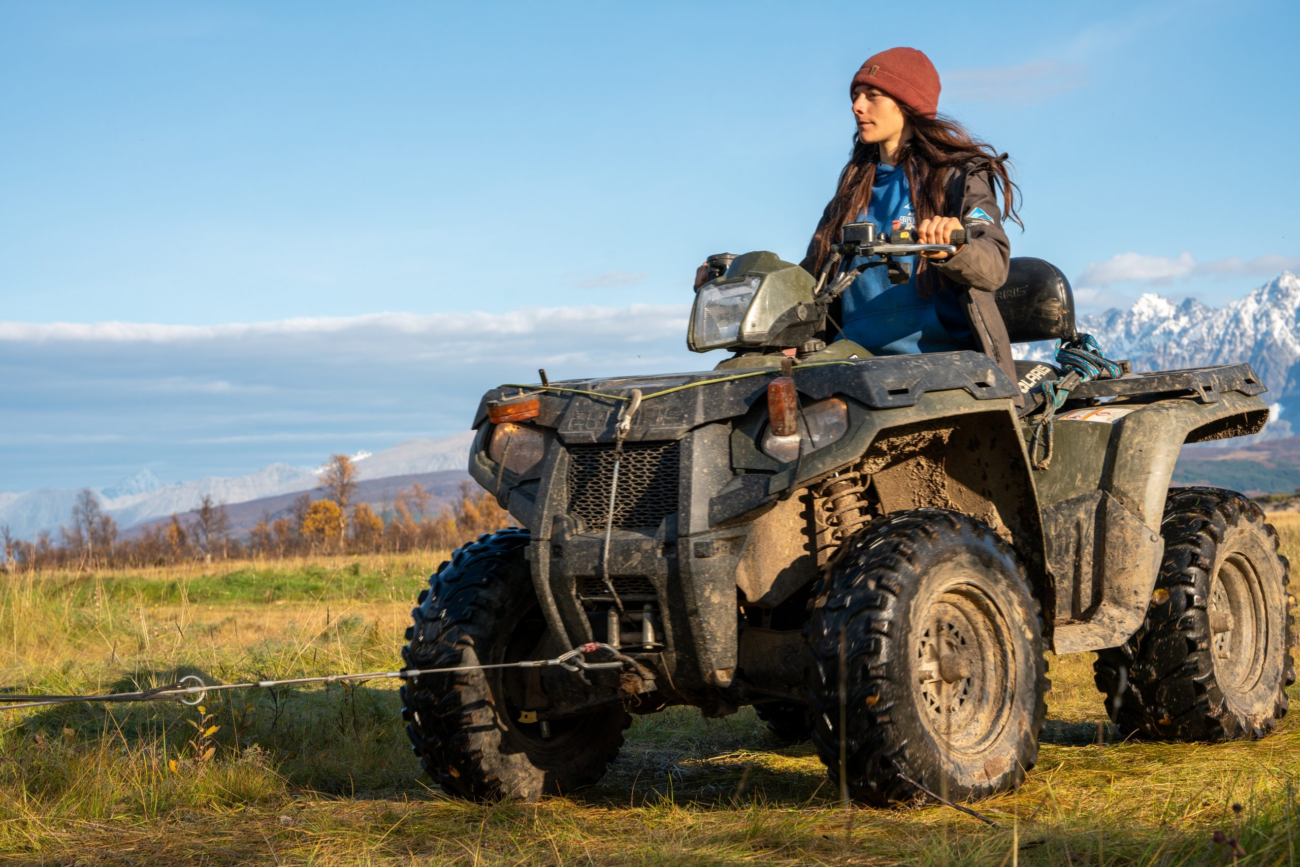 woman driving quad bike in red hat