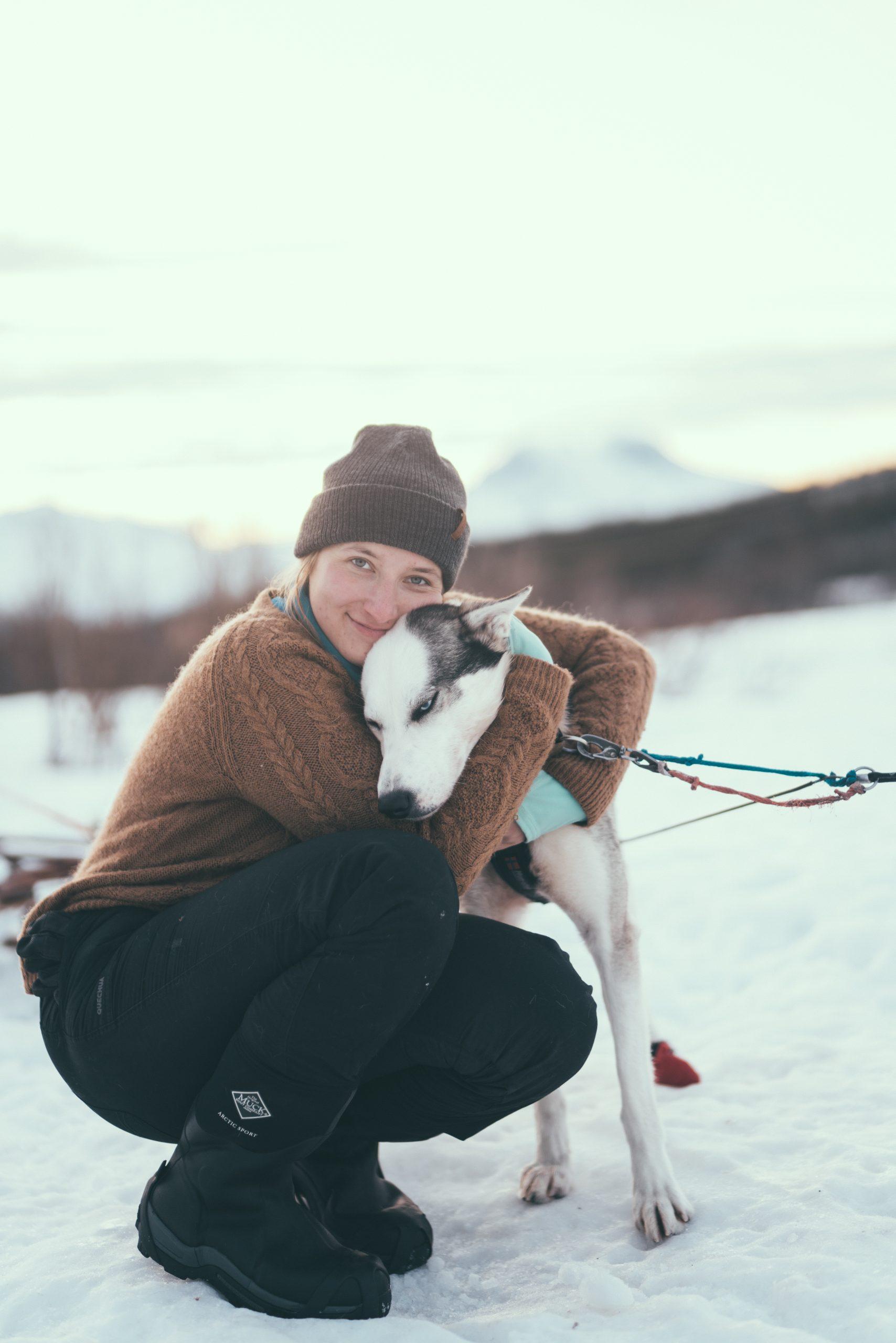 woman cuddling husky in snow
